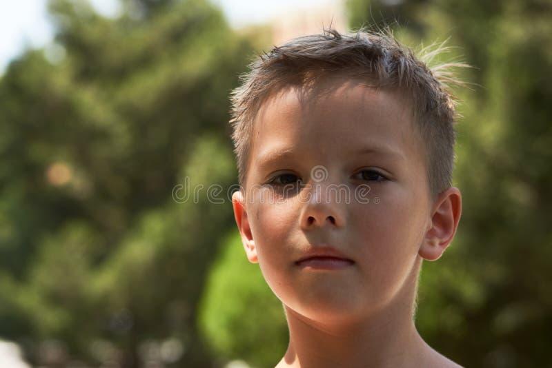 Portrait mignon de petit garçon en parc avec les arbres verts sur le backgro image stock
