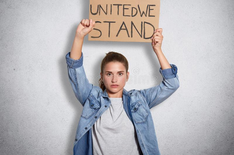 Portrait of militant powerful young feminist showing her fist, holding sign with inscription united we stand in one hand, having. Decisive facial expression stock images