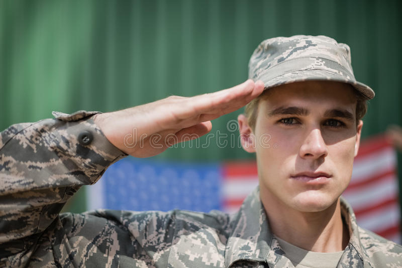 Portrait of military soldier giving salute. In boot camp stock image
