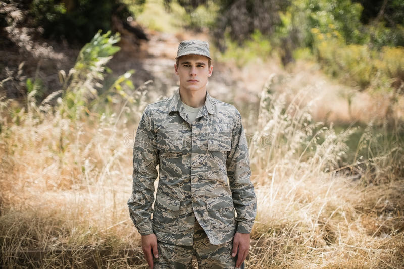 Portrait of military soldier standing in grass stock photography
