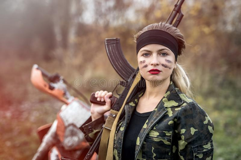 Portrait of military woman holding rifle outdoors royalty free stock photo