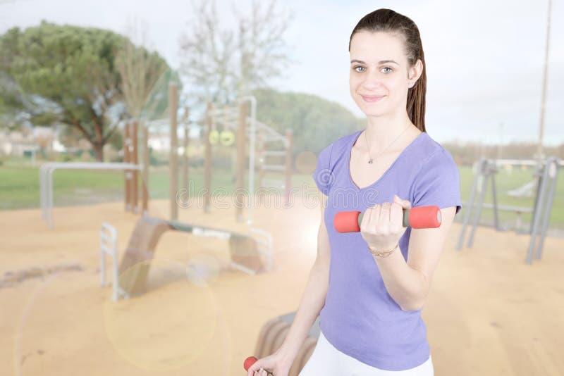 Portrait mince sportif de fille d'ajustement avec l'haltère dans l'exercice extérieur images libres de droits