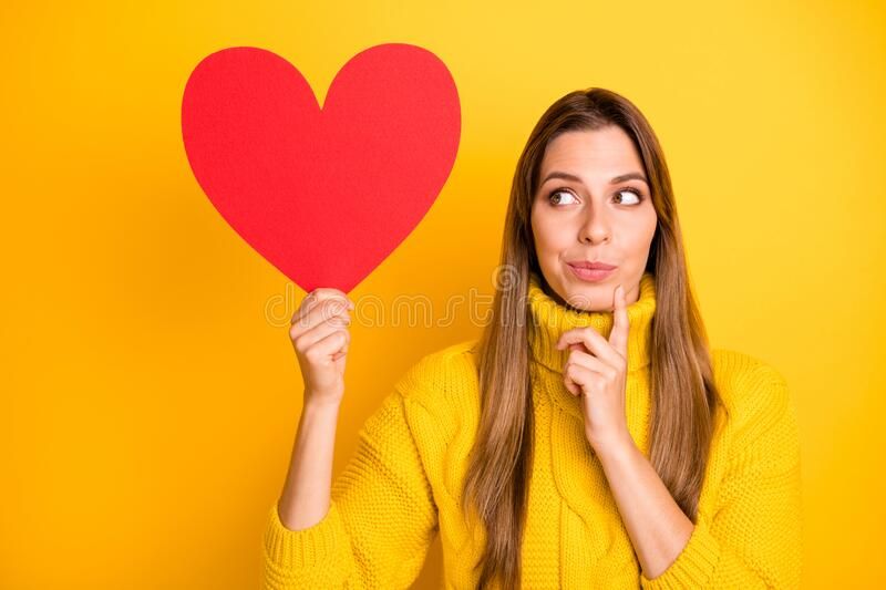 Portrait of minded girl get red big paper card heart from secret admirer think thoughts who he is wear knitted collar. Portrait of minded girl get red big paper royalty free stock photos