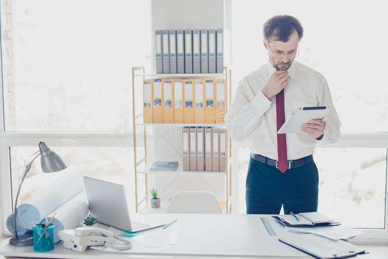 Portrait of minded mature experienced businessman in suit holding digital tablet and thinking about new startup project royalty free stock images