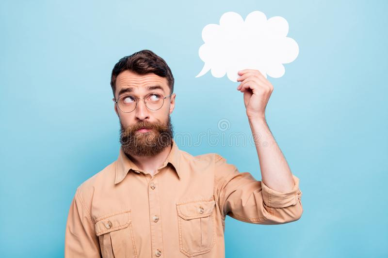 Portrait of minded person holding looking at paper card bubble wearing brown shirt  over blue background stock images