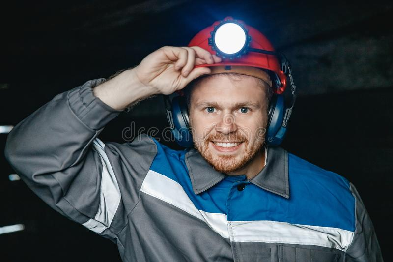 Portrait miner coal man in helmet with lantern in underground mine. Concept industrial engineer royalty free stock photo