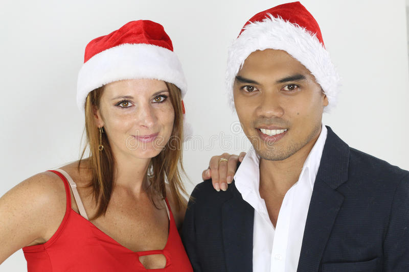 Portrait of a mixed couple posing for Christmas. Over a white background royalty free stock images