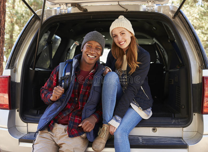 Portrait of mixed race couple sitting in open back of a car royalty free stock photo