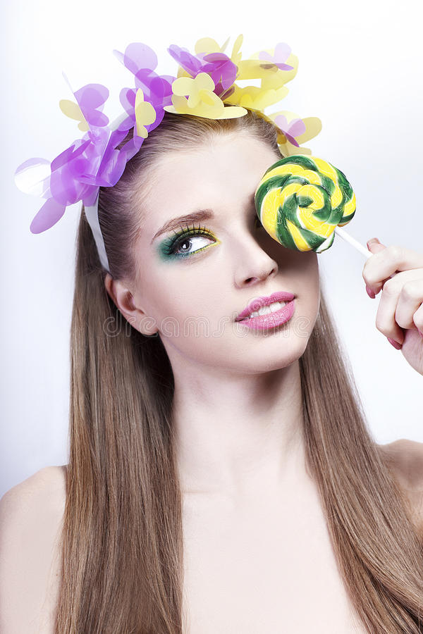 Portrait of a model with colorful make up and candy on white background stock photos