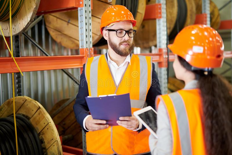 Safety Inspector. Portrait of modern bearded businessman wearing hardhat listening to factory employee while standing in workshop and holding clipboard, copy royalty free stock photography