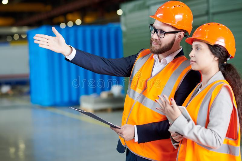 Inspection at Modern Factory. Portrait of modern bearded businessman wearing hardhat talking to female factory worker and pointing away while discussing stock images