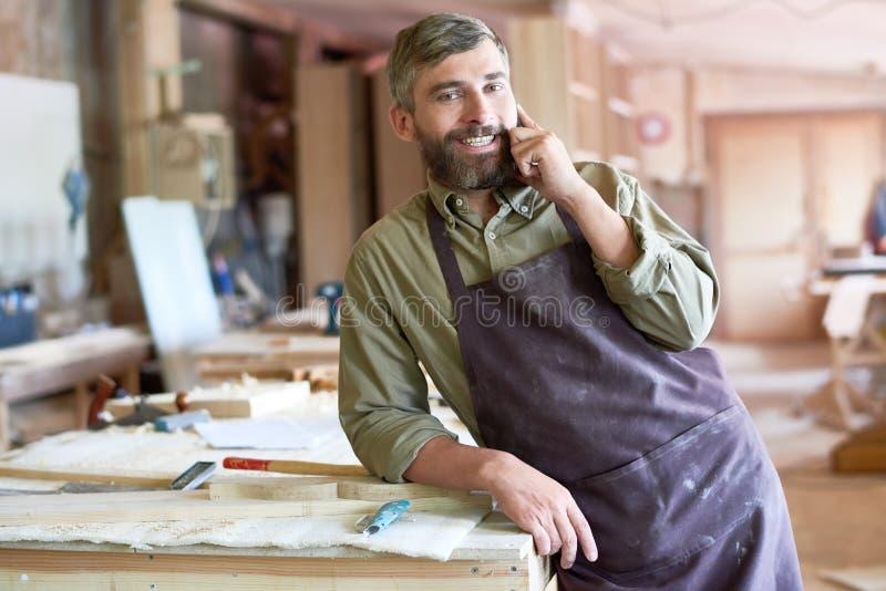 Bearded Carpenter Speaking by Smartphone in Modern Workshop royalty free stock photos