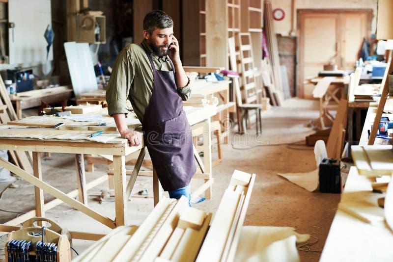 Carpenter Speaking By Smartphone in Modern Workshop stock photos