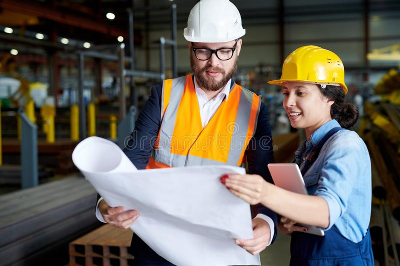 Engineers Studying Plans. Portrait of modern bearded engineer wearing hardhat holding blueprints while discussing production with female worker in factory stock photo