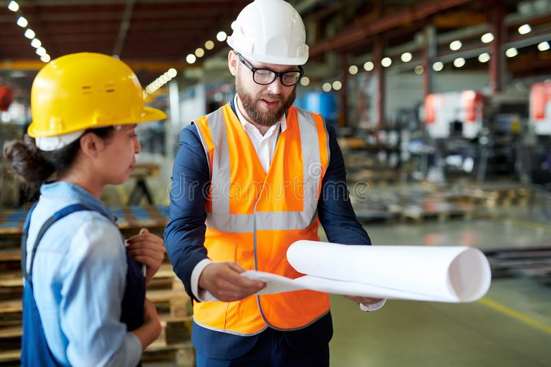 Engineer Holding Blueprints. Portrait of modern bearded engineer wearing hardhat holding blueprints while discussing production with worker at factory, copy royalty free stock photography