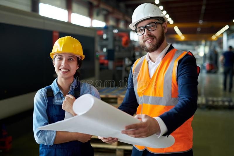 Smiling Engineers Holding Blueprints. Portrait of modern bearded engineer wearing hardhat holding blueprints smiling cheerfully while discussing production with stock photo