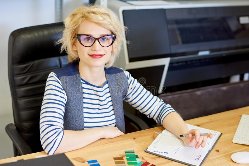 Graphic Designer at Desk. Portrait of modern blonde woman smiling at camera while working on graphic design in printing shop or publishing company, copy space royalty free stock image