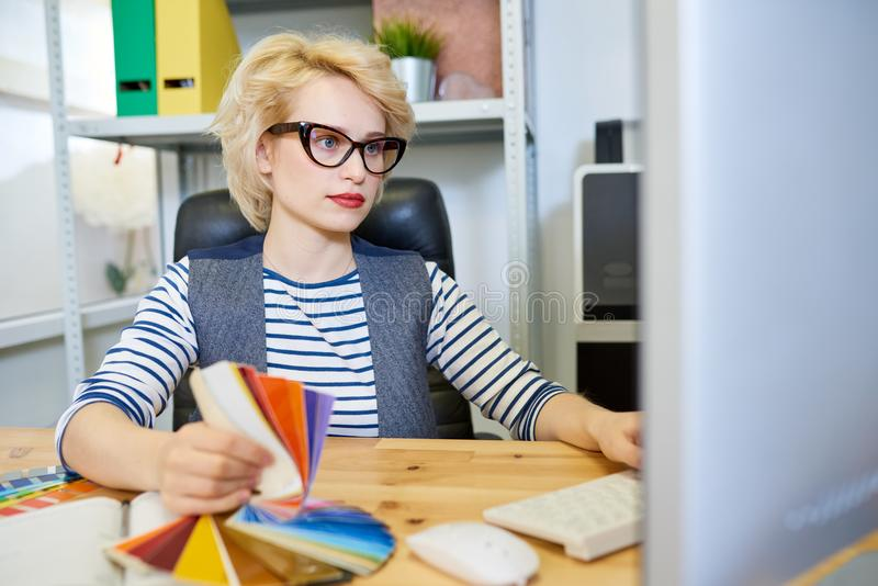 Graphic Designer Using PC. Portrait of modern blonde woman using computer at desk while working on graphic design in printing shop or publishing company, copy royalty free stock photos