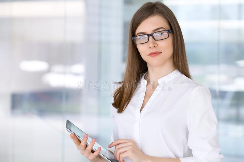Portrait of modern business woman working with tablet computer in the office.  royalty free stock image