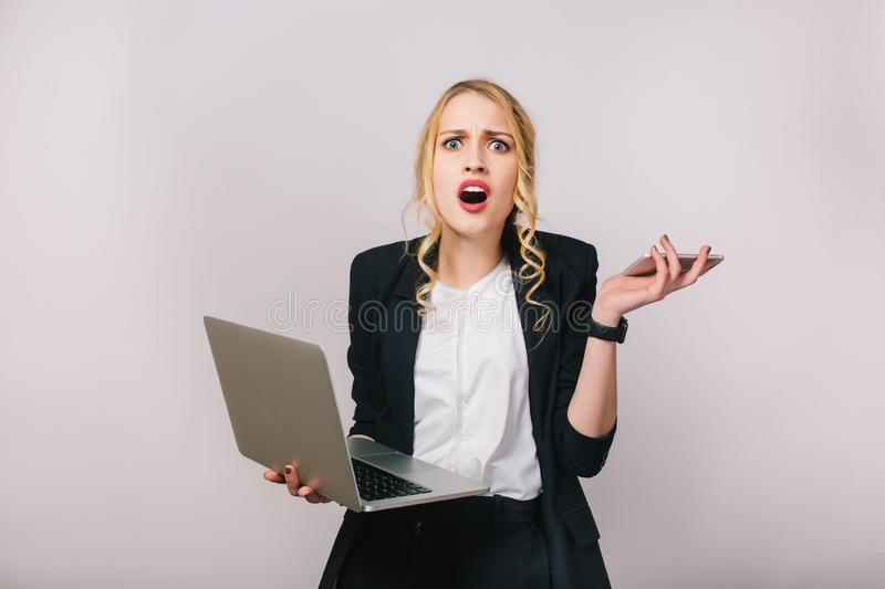 Portrait modern pretty blonde office woman in white shirt and black jacket on white background. Working with laptop stock photography