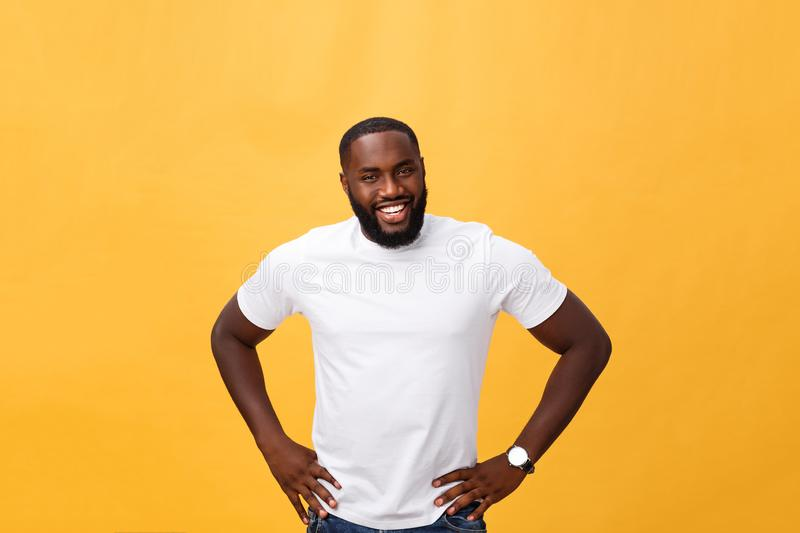 Portrait of a modern young black man smiling standing on isolated yellow background stock images