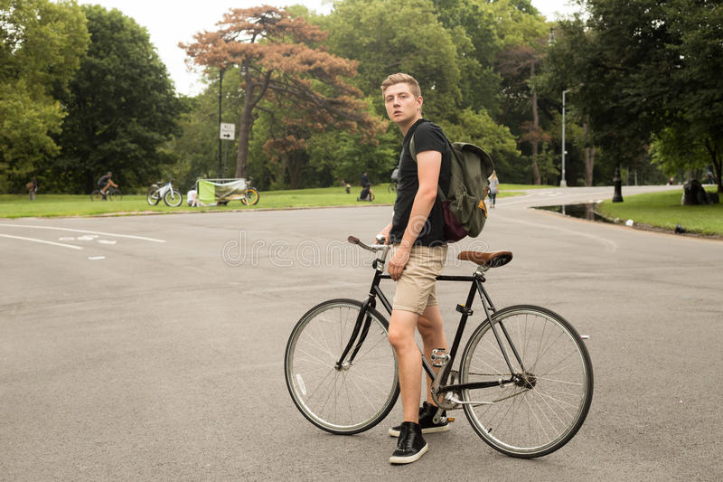Portrait of modern young college student with bike in the park royalty free stock image