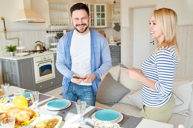 Happy Couple Setting Dinner Table stock photo