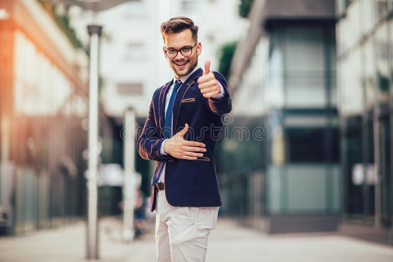 Modern young smiling businessman giving thumb up outdoor royalty free stock photos