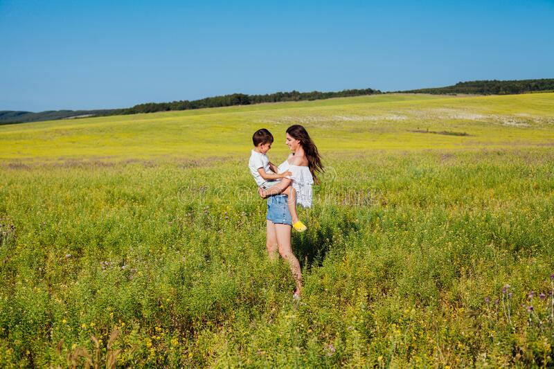 Portrait of a beautiful mom and son on a walk on nature field road royalty free stock images