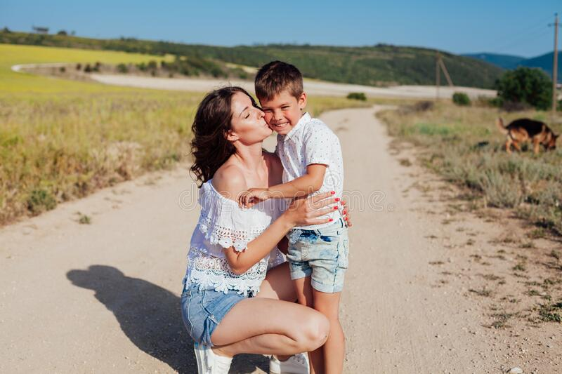 Portrait of a beautiful mom and son on a walk on nature field road royalty free stock photos