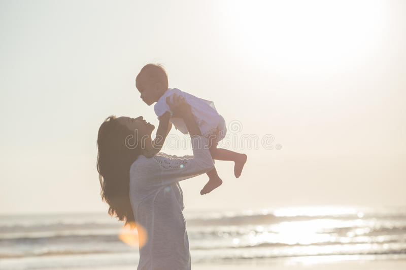 Portrait of mother and baby in the beach at sunset stock images