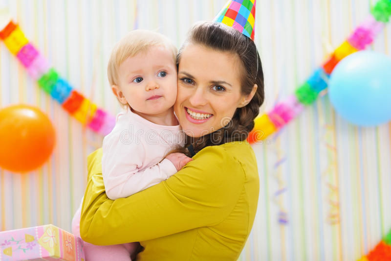 Portrait of mother and baby at birthday party. Portrait of happy mother and baby at birthday party stock photo