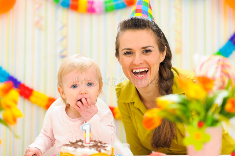 Portrait of mother with baby eating birthday cake. Portrait of mother with baby girl eating birthday cake stock image
