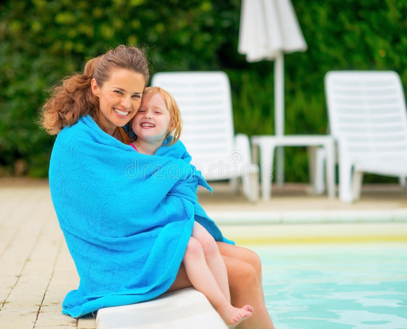 Portrait of mother and baby near swimming pool. Portrait of happy mother and baby girl wrapped in towel sitting near swimming pool stock photography