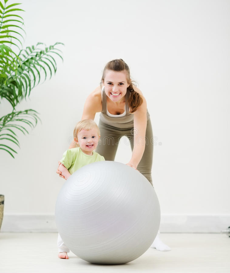 Portrait of mother and baby playing with ball royalty free stock photos