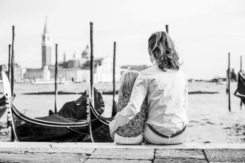 Mother and baby sitting on grand canal embankment in royalty free stock photos