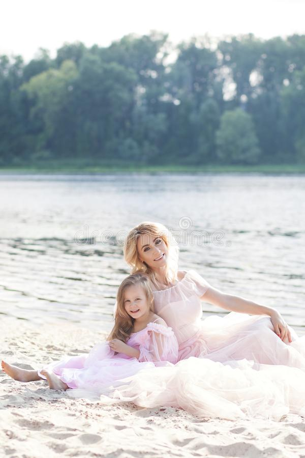 Portrait of a mother blonde and her daughter in beautiful dresses on the sand with a lake on the background. Happy family enjoying royalty free stock image