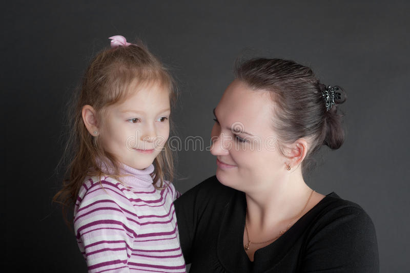 Portrait of mother with the daughter. On a black background royalty free stock photos
