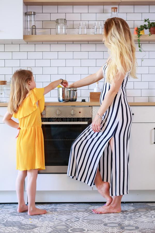 Portrait of mother and daughter cooking in kitchen royalty free stock photography