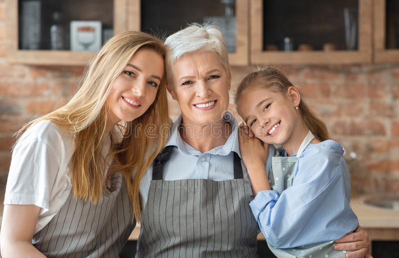 Portrait of mother, daughter and grandmother embracing at kitchen royalty free stock image