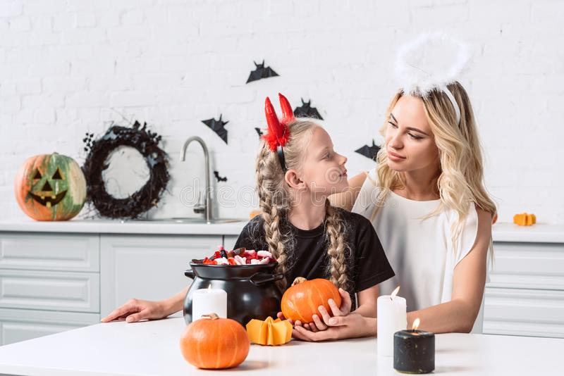 portrait of mother and daughter in halloween costumes at table with sweets in black pot in kitchen stock photos