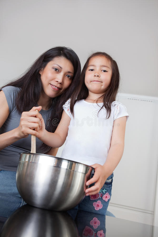 Portrait of mother and daughter in kitchen stock photography