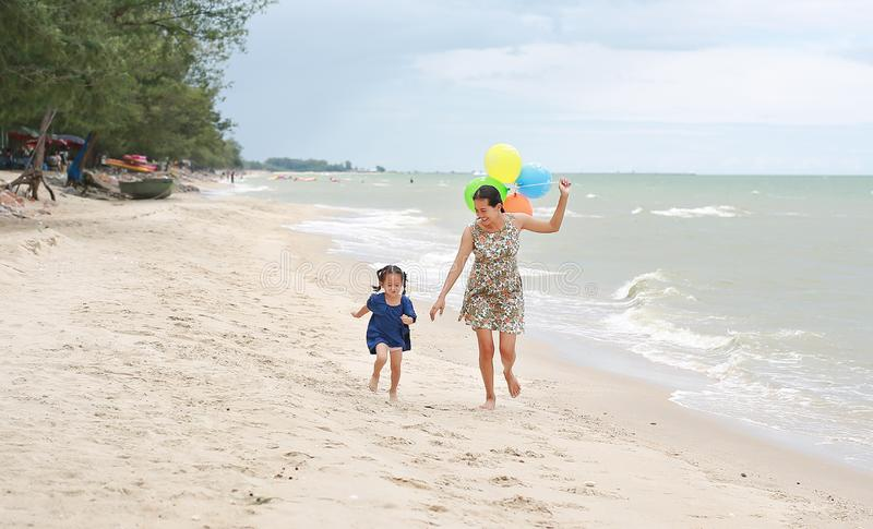 Portrait of Mother and daughter running on beach with colorful balloons in mother hand. Holiday concept stock photos