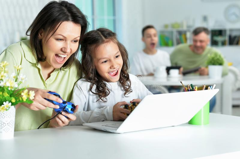 Portrait of mother and daughter using laptop together playing game stock photos