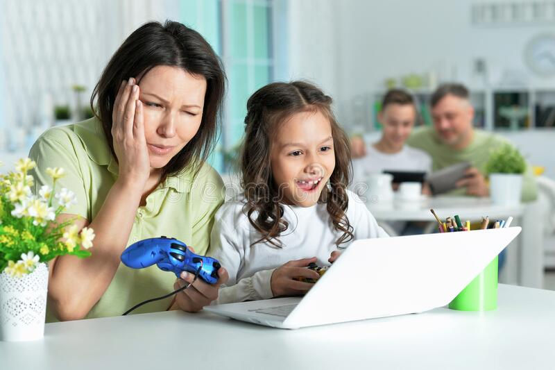 Mother and daughter using laptop together playing game royalty free stock photos