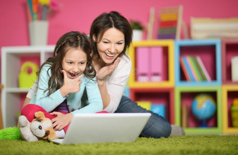 Portrait of mother and daughter using laptop together royalty free stock photos