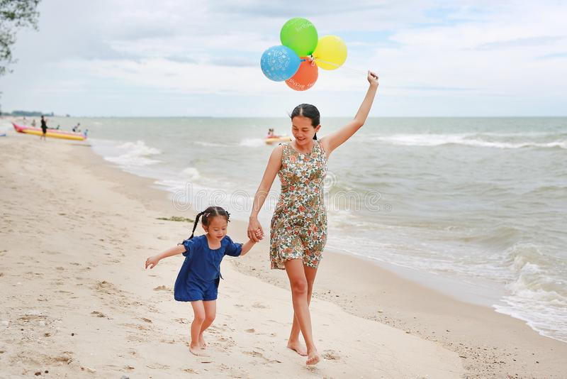 Portrait of Mother and daughter walking on beach with colorful balloons in mother hand. Holiday concept royalty free stock images