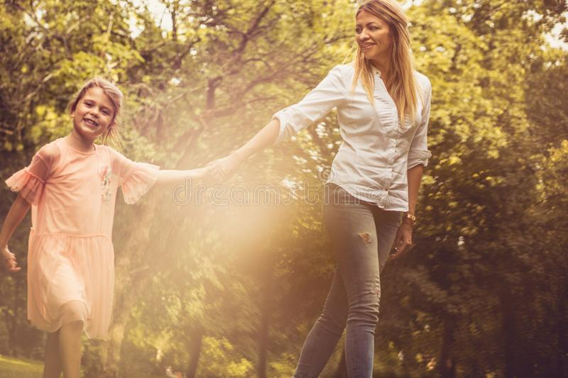 Portrait of mother and daughter walking trough nature. Spring season royalty free stock photo