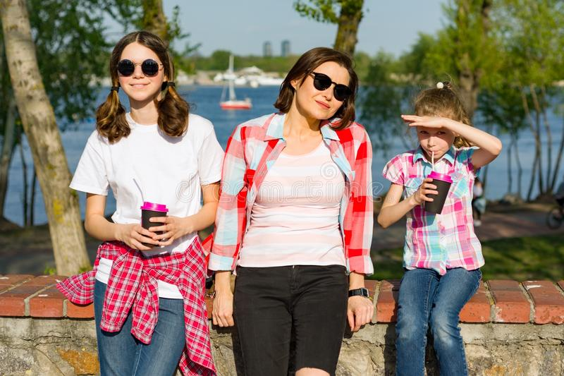 Portrait of mother and daughters. Drinking ice tea stock photo