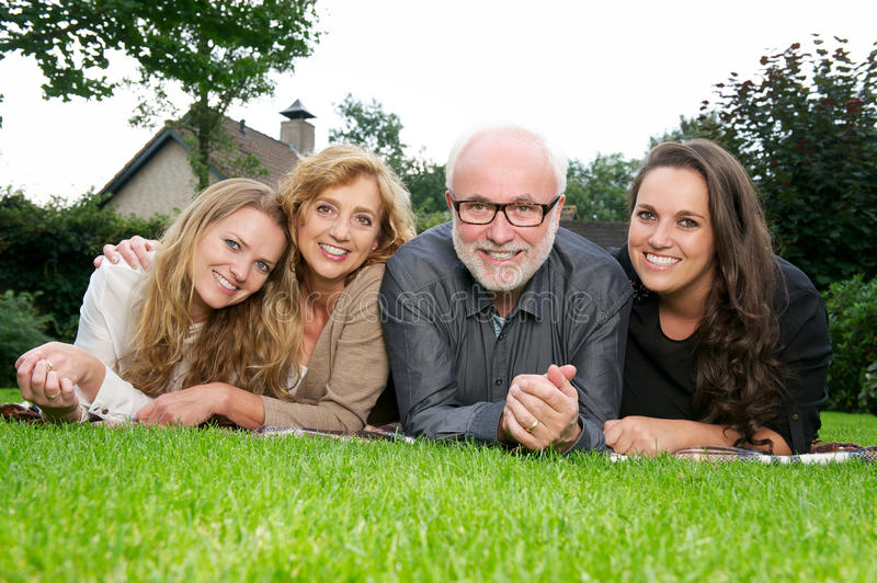 Portrait of a mother and father smiling together with two older daughters stock photography